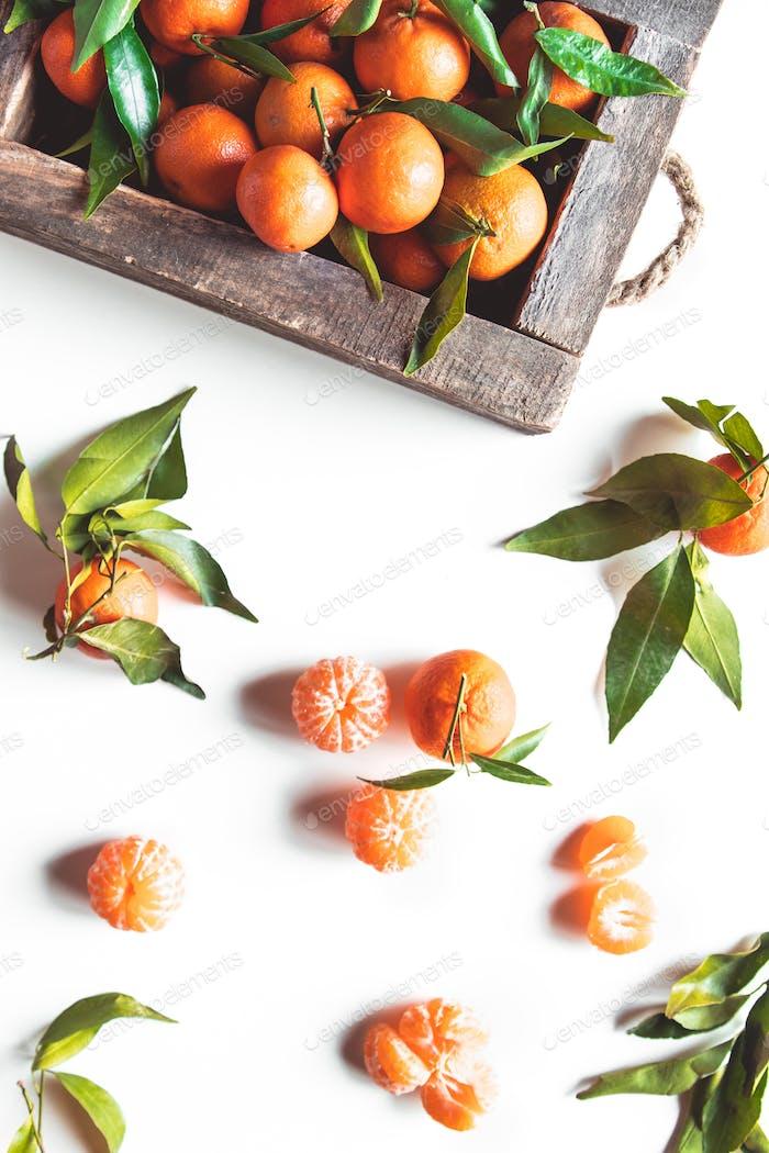Mandarinen mit frischen Blättern in Holzkiste isoliert auf weiß, isoliert auf einem weißen, Draufsicht