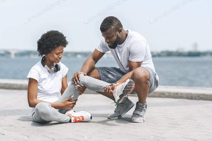 Afro Guy Helping Woman With Injured Ankle At Riverbank