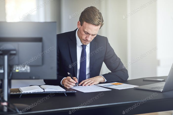 Businessman reading through paperwork at his office desk