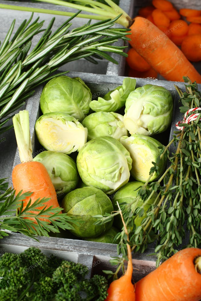 Fresh raw brussels sprouts, carrots, rosemary, thyme and parsley in wooden box