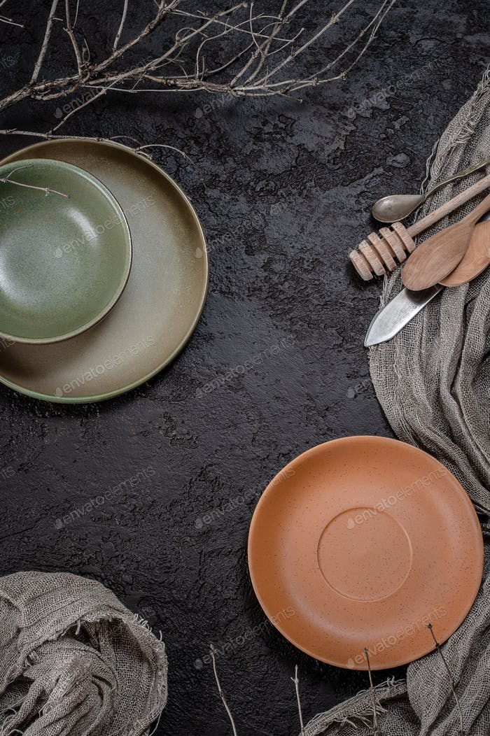 Plates, cutlery and cloth on a dark brown textural background. B