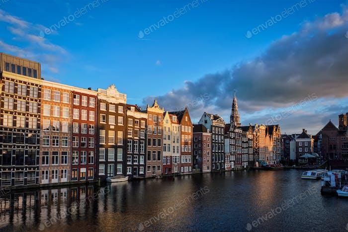 Hütten und touristische Boote am Amsterdamer Kanal Pier Damrak auf Sonnen
