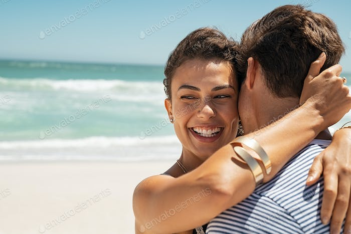 Happy woman embracing her boyfriend at beach