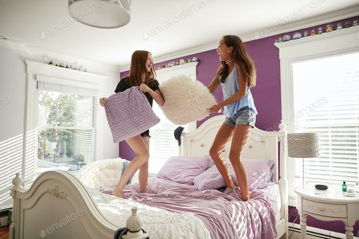 Two teenage girls standing on a bed having a pillow fight
