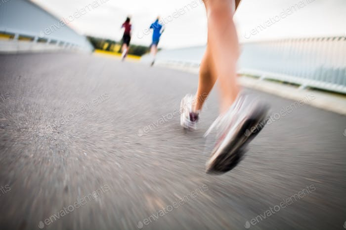 Young woman jogging outdoors - detail of the