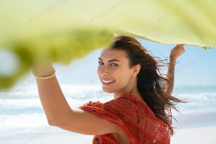 Smiling woman holding green scarf at beach