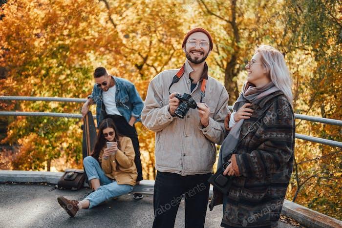 Cuatro amigos que pasan las vacaciones juntos en el parque de otoño