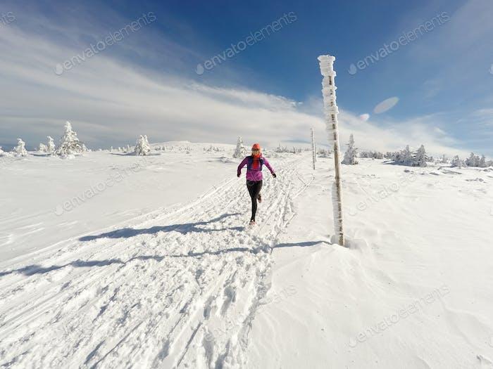 Lauffrau auf Winterweg, Schnee und weiße Berge