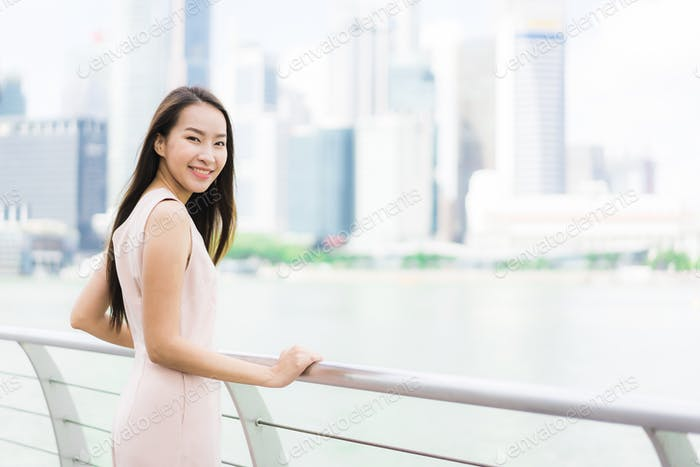 Beautiful asian woman smile and happy to travel in singapore cit