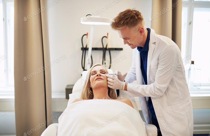 Doctor injecting botox around the eyes of a mature woman