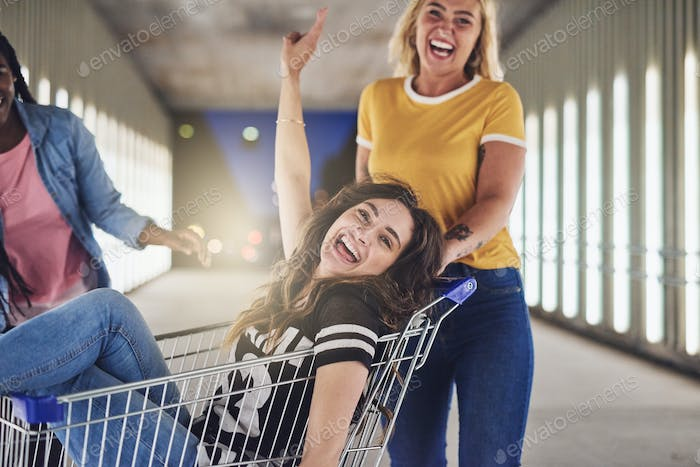 Girlfriends playing with a shopping cart together at night