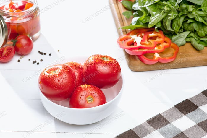 Canned tomatoes and fresh tomato on white background