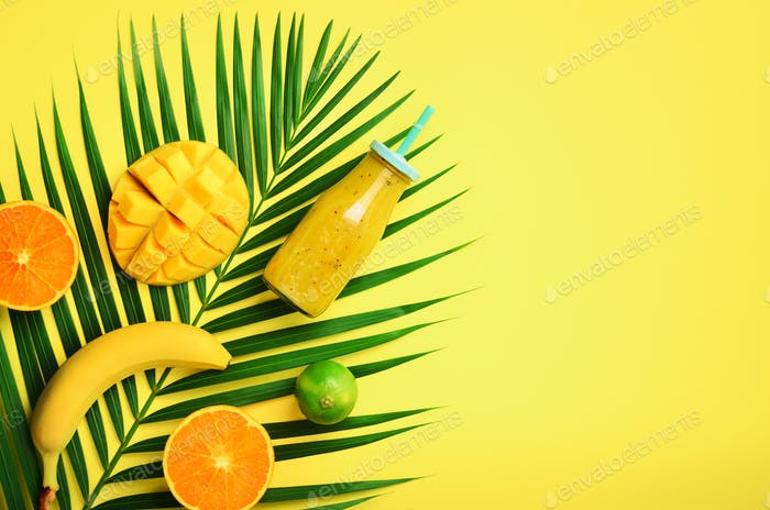 Fresh orange, banana, pineapple, mango smoothie and juicy fruits on palm leaves over yellow