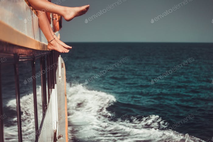 Young people chilling in boat. Only legs close up