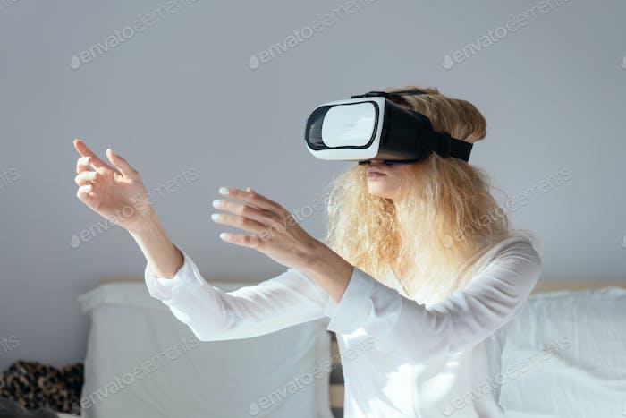 Mädchen sitzt auf einem Bett mit VR-Headset