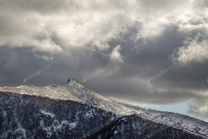 Cloudscape over a Snowy Rocky Peak