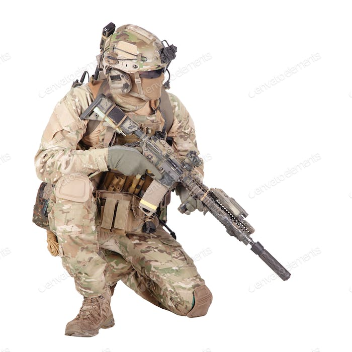 Soldier with rifle standing on knee studio shoot