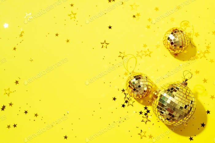 Creative Christmas concept. Shiny gold disco balls over yellow background. Flat lay, top view. New