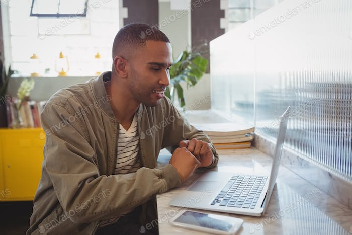 Businessman looking into laptop at counter