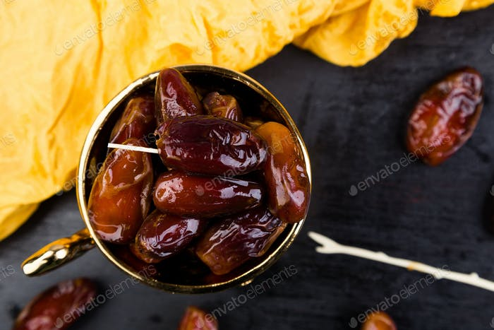 Dry fruit dates in golden cup near slate black heart. Copy space.