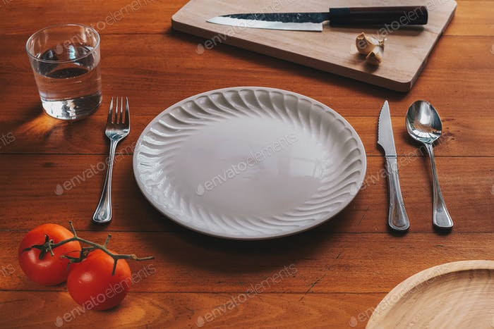 Porcelain plate and cutlery against a wood background with mediterranean elements