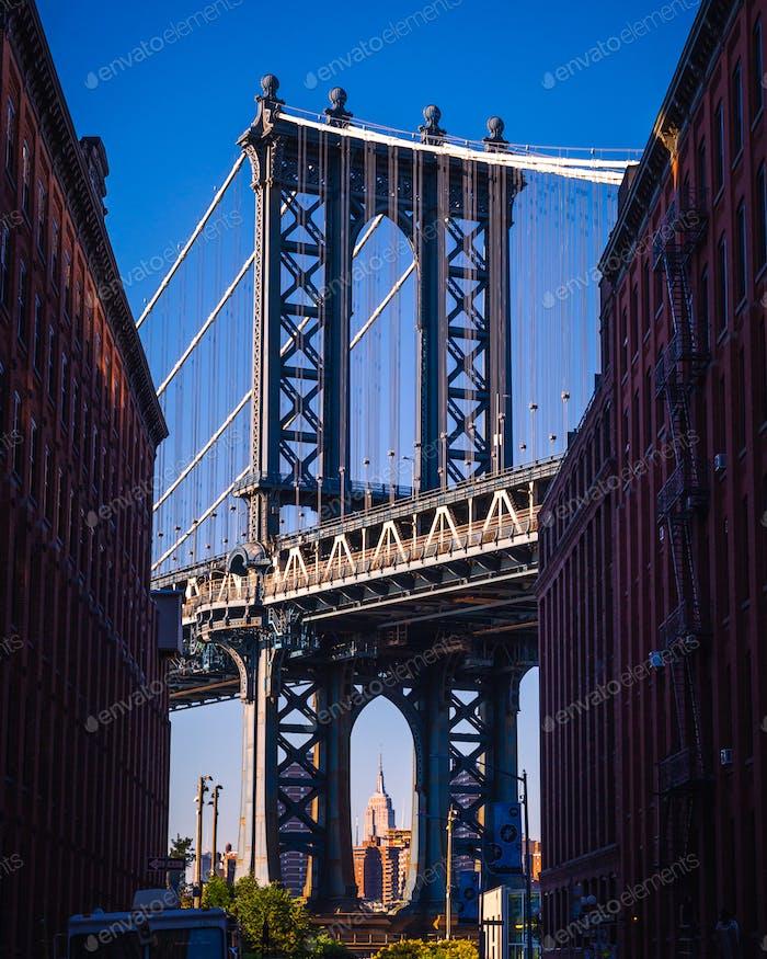 Puente de Manhattan visto desde un estrecho callejón cerrado por dos ladrillo