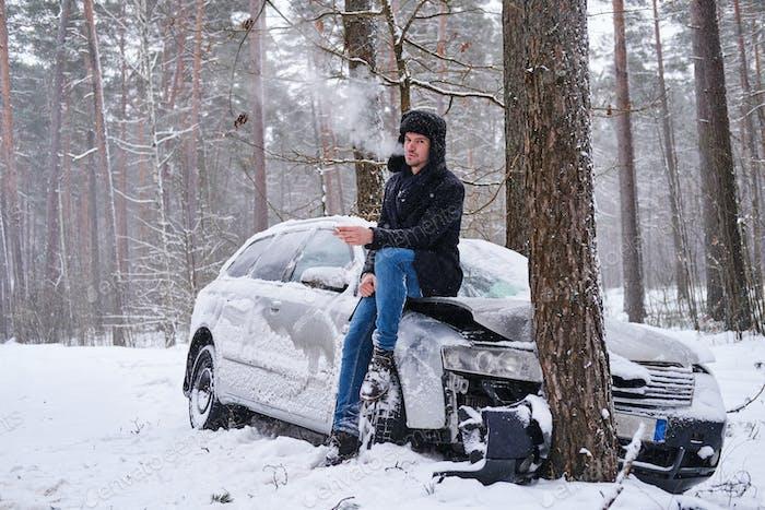 Der Fahrer raucht neben dem zerstörten Auto eine Zigarette.