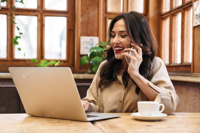 Image of happy adult woman talking on cellphone and working with laptop