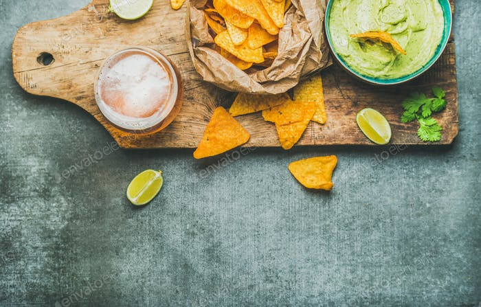 Guacamole sauce, corn chips, beer in glass, copy space