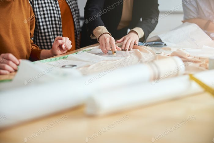 Talented dressmakers applying their pattern to the fabric