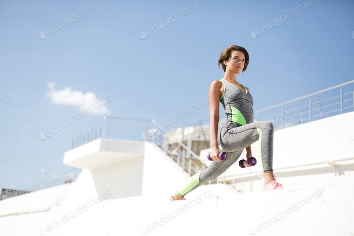 Thoughtful woman in modern gray sport suit doing exercise with dumbbells and looking aside