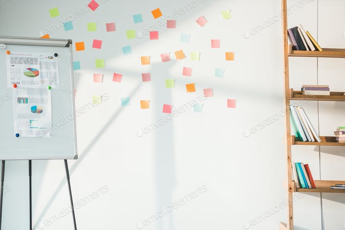 whiteboard with charts and white board with sticky notes in modern light office