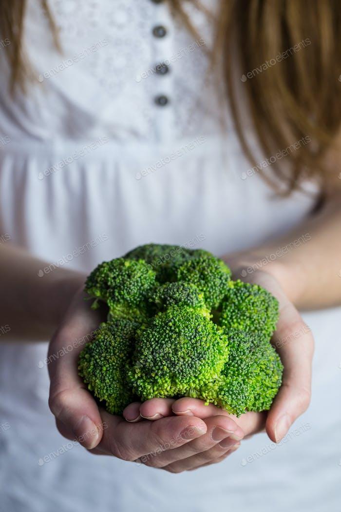 Woman showing fresh green brocolli in close up