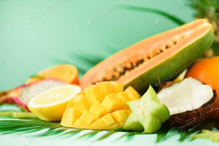 Assortment of exotic fruits on turquoise background. Detox, vegan food, summer concept. Papaya
