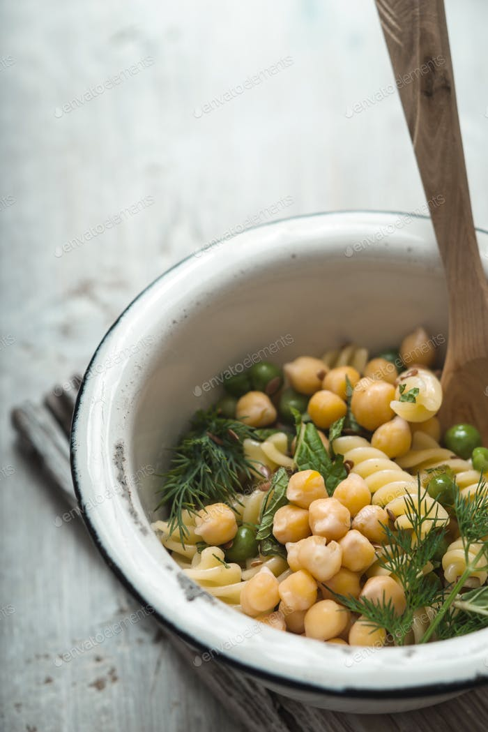 Salad with fusilli, chickpeas and peas in bowl on a white table