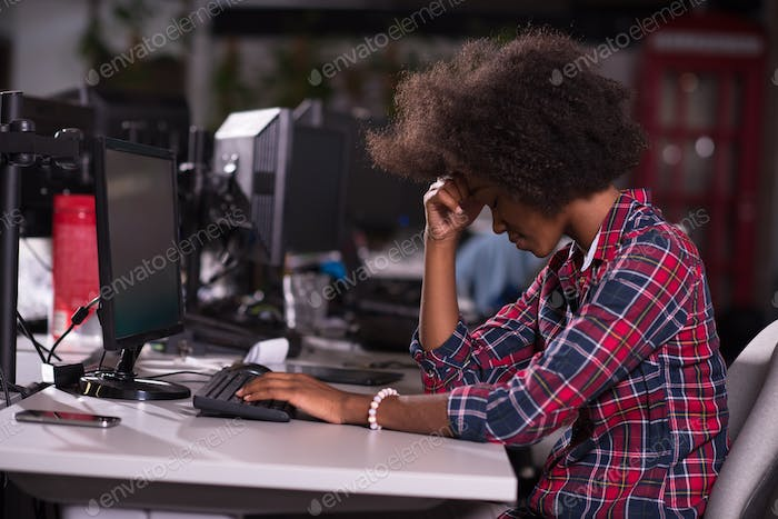 a young African American woman feels tired in the modern office