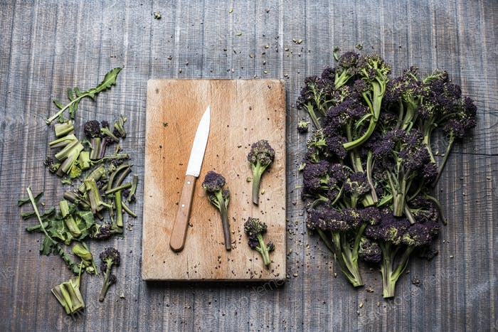 High angle close up of purple sprouting broccoli, knife and wooden cutting board.