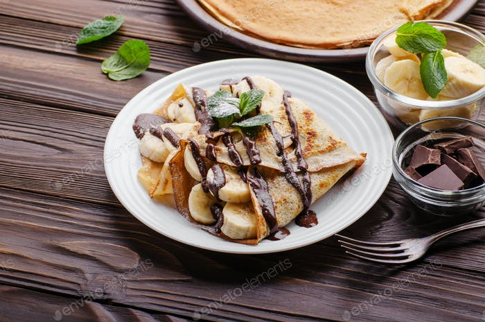 French crepes with chocolate sauce and banana in ceramic dish on