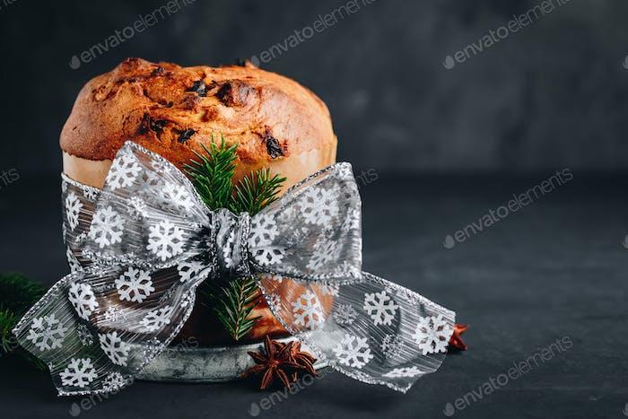 Panettone Kuchen. Traditioneller italienischer Weihnachtskuchen mit getrockneten Früchten auf dunklem Steinhintergrund