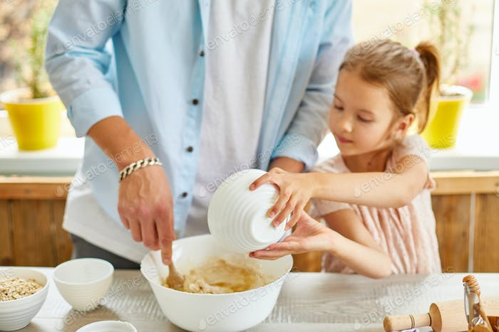 Father and daughter preparing dough together in kitchen