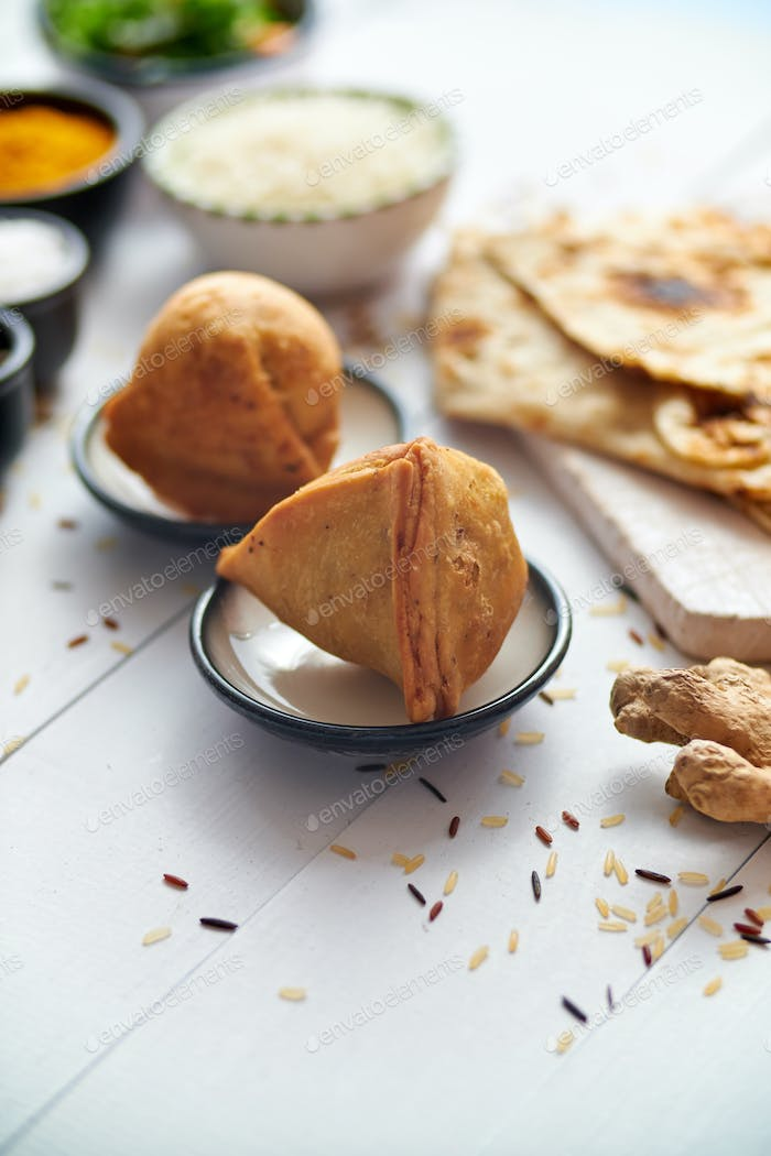Traditional Indian Food snack Samosa served in a plate on a white wooden table
