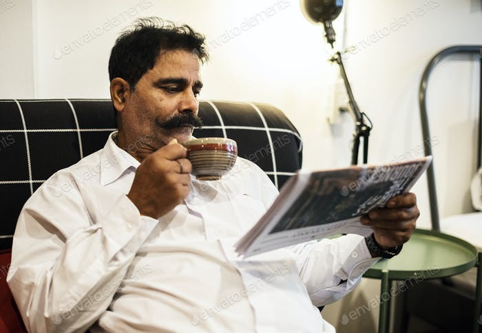 Indian man reading newspaper