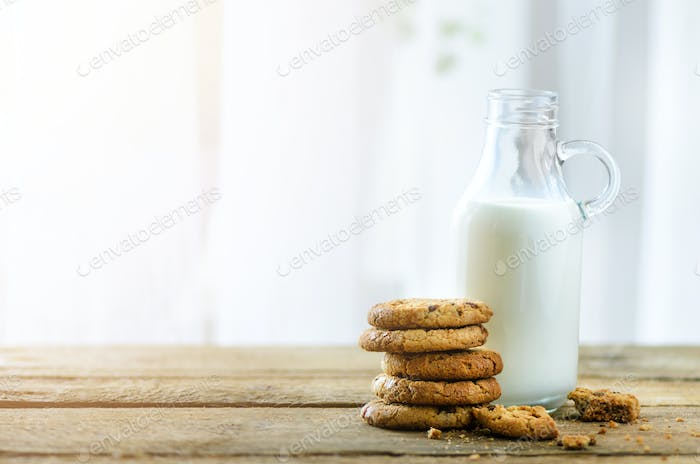 Chocolate chip cookies, bottle and glass of milk on wooden table near window, white background