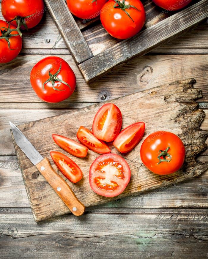 Schneiden Sie Tomaten mit einem Messer auf ein Schneidebrett.