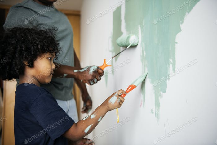 Black family painting house wall