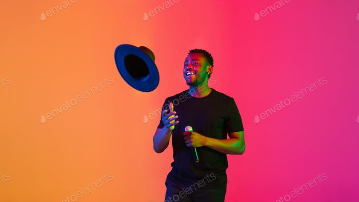 Young african-american musician singing, dancing in neon light, flyer
