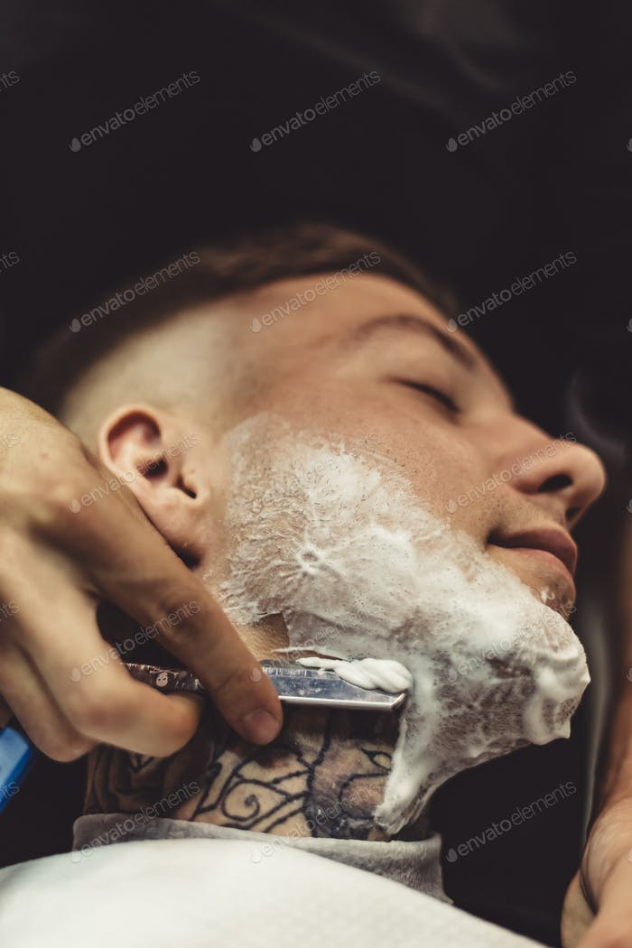 Anonymous man shaving client