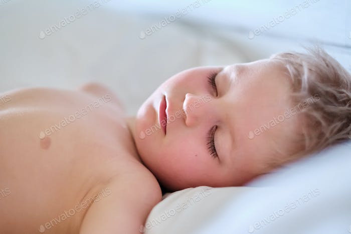 Toddler boy sleeping on pillow