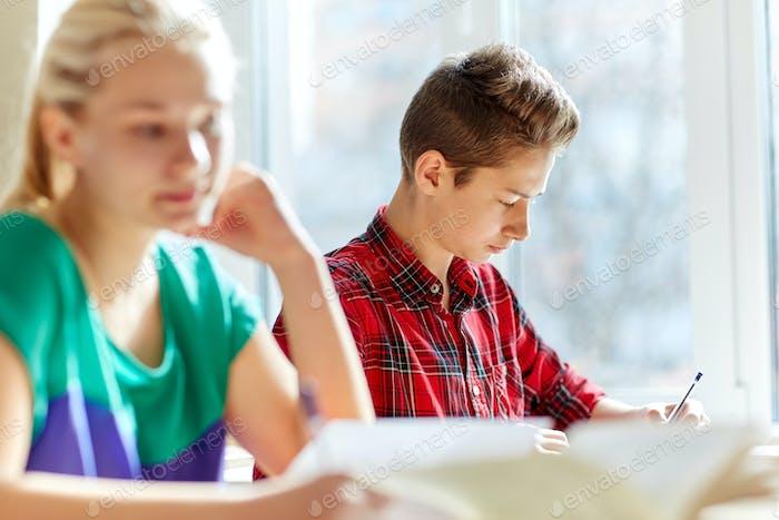 Grupo de estudiantes con libros de escritura de la escuela de la prueba