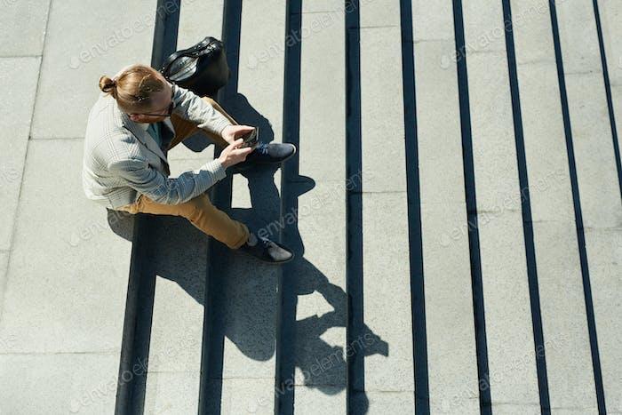 Stilvoller Geschäftsmann sitzt auf der Treppe
